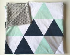 Perfect for a gender-neutral gift or nursery, this modern minky blanket is made of triangles and geometrics in mint, black, white, navy, mustard and olive (top is one whole piece; not triangles quilted together). TOP FABRIC: Smooth minky - very soft to the touch, colors are fade-resistant. BACK FABRIC: Bubble dot minky in your color choice. Very soft, has a great bubbly texture for little fingers. SIZE: Choose from drop-down menu.  **This blanket is made-to-order. Please allow 2-3 weeks for…
