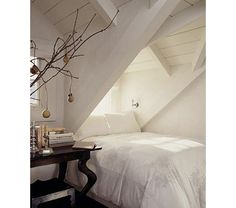 white attic bedroom with exposed beams and a dark wood side table - Home and Garden Design Ideas
