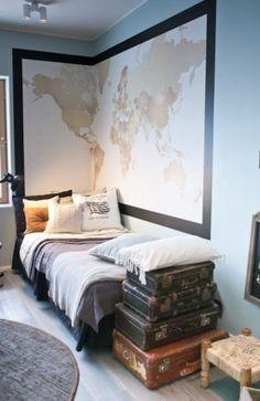 Stoere slaapkamer met een grote landkaart en vintage koffers.