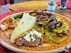 Chilaquiles la Fundición - Bañados en salsa verde, gratinados con queso, fajitas de res y chiles toreados en rajas. Se acompañan con frijoles refritos y cebollita asada.