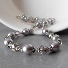 Silber, die mit silbrig grau 10 mm Glasperlen Perlenketten gemacht sind gepaart mit rauchigen graue Kristalle mit silbernen Blitz-Beschichtung. Ich habe mit Akzent, die Perlen und Kristallen mit kleinen antikisiert Silber Beadcaps an jedem Ende und Abstand ihnen auseinander mit winzigen Runde Silber-Perlen. Die Perlen sind auf flexiblen Sicke Draht eingefädelt. Das Collier schließt mit einem Karabinerverschluss Sterling silber und beinhaltet 1,5 Zoll Länge Sterlingsilber Anpassung Kette mit…