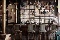 Multi-coloured rattan stools made in France sit at the bar, adding a hint of the French bistro. The front of the bar has been paneled with c...