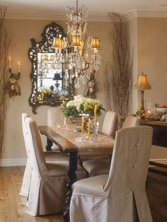 French country dining room with rustic table, slipcovered chairs & crystal chandelier