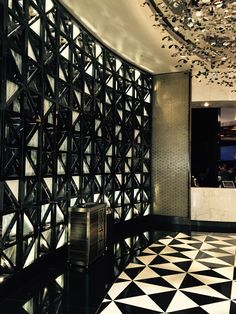 MY CHOSEN DISCUSSION PICTURE 2: This creative partition wall by 'Wunda projects Australia' adopts the use of small geometrical triangles made from clear and opaque glass triangles, with cutouts held together by a black metal frame. The arrangement is set to counterbalance the floor pattern in contrasting black and white. The glitzy and glamorous ceiling feature made from shiny sheet metal is bent to create a leaf-like effect and further add to the rooms complex nature.