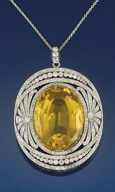 Circa 1905 diamond and citrine diamond pendant   The oval citrine within a diamond openwork panel with palmette decoration and old-cut diamond collet detail, to a fine link chain.