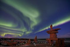 Photo of an inukshuk on the shores of Hudson Bay with the Aurora borealis streaming above.