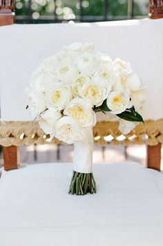 Elaborate White Wedding: The bride's gorgeous wedding bouquet of white peonies is wrapped in a creamy silk ribbon.