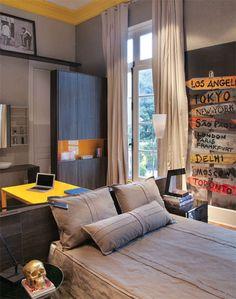 Suíte do Rapaz. A colcha que forra a cama é de lona de caminhão. Na parede, o painel adesivado traz a imagem divertida de skates grafitados com nomes de diferentes cidades.