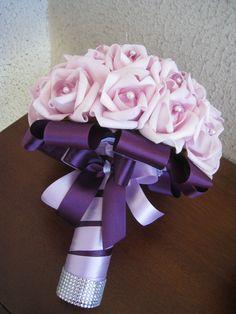 Lindo Buquê produzido com rosas super delicadas de e.v.a. em Lilás, pétalas fininhas como uma pétala de rosa natural, aparência e textura super próximas às rosas naturais! <br> <br>Detalhes do Buquê: <br>*Aproximadamente 36 rosas. <br>* Renda na base do buquê; <br>* Fitas de cetim envolvendo a haste, mesclando entre lilás e roxo; <br>* Laço duplo de cetim lilás e roxo, super delicado. <br>* Strass no cabo. <br>* Meia - Pérola em todas as Flores. <br>* Pontos de Luz de Pérolas Flor…