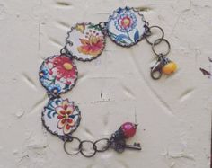 Bright and pretty bracelet crafted from the floral lid of a vintage tin box. It features a gorgeous spring green background with flowers of hot pink and blue. It measures 6.5-7.0 inches in length, depending on the jump ring the lobster clasp attaches to. The length includes the clasp. It is accentuated with a blue bead and key charm on the end. It will come wonderfully packaged in a fresh floral envelope...all ready to give. Tin is the designated gift for the ten year wedding…