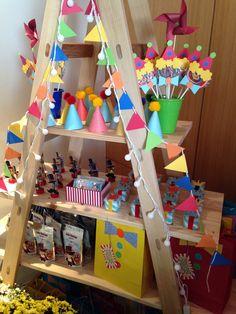 Detalhes da estante de personalizados/lembrancinhas, o cordão de luzes coloridas e as bandeirolas deixaram tudo mais divertido e alegre.