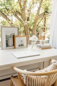 Beautiful workspace and home office design in front of a window, white desk, desktop styling, woven chair. Office goals!