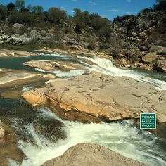 The Pedernales river cascades over layered limestone to create the picturesque Pedernales Falls State Park in the hill country.
