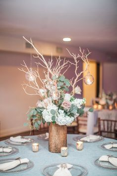 Wedding Table Centerpiece and Decor Our wooden cylinder vase with natural manzanita branches, hanging glass votives and floral of ivory hydrangea, Earl Grey roses, white stock, silver dollar eucalyptus and Amnesia roses. Silver glass beaded chargers, ivory sateen napkins and bronze starburst napkin rings.