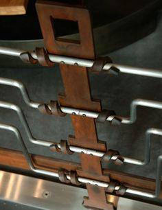 Poteaux de garde-corps en ferronnerie contemporaine alliant acier oxydé et inox brossé