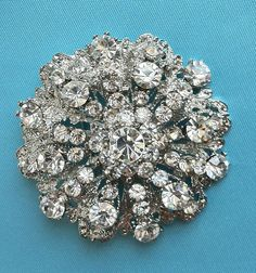 Broach - give them as gifts and they wear on dress - more memorable than earrings & adds a tie in to you and some glam to their dresses??