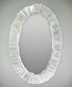 Oval Selenite Mirror - Within the Oval Selenite Mirror may be found a reflection of many things: the visage of someone beloved, a posy of newly-cut blooms, a fragment of cerulean sky on a summer day. The center glass boasts a frame of rectangular selenite crystals that lend the piece a touch of refined glam befitting the transitional decor of a suite, entranceway, or alcove.