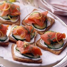 Open Faced Smoked Salmon Sandwiches  Cocktail rye bread slices  sour cream & cream cheese mixed together  1 cucumber sliced  sliced smoked salmon  lemon peel curls  fresh dill