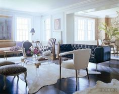 """""""The best way to make a room feel larger is to buy smaller scale furniture. Notice in the photo...that the black sofa is really a loveseat. The scale and proportions of the sofa and the dainty armchairs create more circulation area. Large sofas, armchairs and tables will make a small room feel crowded, whereas properly scaled furniture won't. Also, leggy furniture works much better in a small space than furniture that sits on the ground."""""""