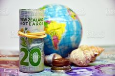 New Zealand Money (NZD); Saving for a World Holiday A mixture of New Zealand Bank Notes (NZD) and coins with a world globe and shells in the background for a Saving for a World Holiday concept. All Australasian Currencies Stock Photo Bank Financial, World Globes, Holiday Photos, Photo Illustration, Image Now, Royalty Free Images, New Zealand, Saving Money, Shells