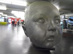 """Dia"" (Day) a giant baby's head sculpture by Antonio Lopez in Puerta de Atocha Railway Station, Madrid, Spain."