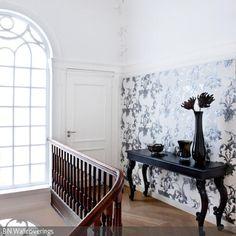 Die Ornament-Tapete in Schwarz-Weiß legt, gemeinsam mit der Konsole im neobarocken Stil, einen edlen Touch über den Flur.  - mehr auf roomido.com