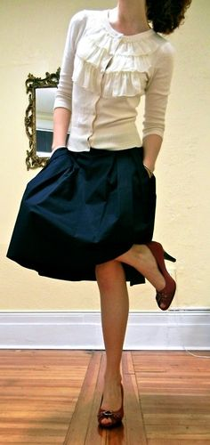 Ruffled cardigan, dark blue skirt and cute red-orange heels.