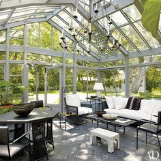 Indoor-Outdoor Living A chandelier from Christie's 2013 Colefax and Fowler sale serves as the conservatory's centerpiece; a Palecek club chair joins an R. E. Steele Antiques cocktail table, and an Hermès blanket accents the sofa