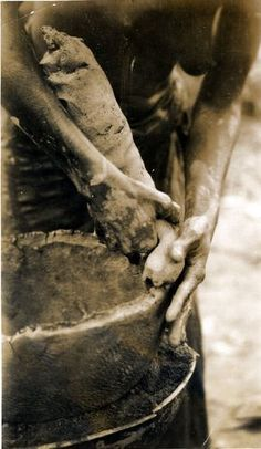 Nigeria, Yoruba pottery-making. Close-up of hands of adult female forming pot, pressing on roll of clay. Pot on platform [?], female wearing cloth around lower body. Medium: Gelatin silver print.