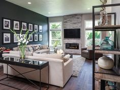 A sophisticated, modern living room features a  dark accent wall and fireplace that adds a cozy feel on HGTV.com.