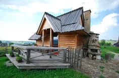 This is and adorable tiny log cabin in Poland. Outside, you'll find a traditional-looking square home with a cozy gable metal roof and stone chimney. The house is made of logs and on the insi…