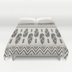 A modern and trendy bohemian design featuring a tribal pattern and feathers in a soft black and cream color scheme. tribal, feathers, bohemian, boho, modern, trendy, chic, black, cream