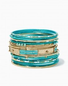 Hit the bangle bonanza with a set of stackable narrow bangles in a variety of shimmering textures and glossy trims.