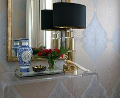 Eclectic foyer design with metallic silver & gold wallpaper, CB2 Peekaboo Console Table, gold leaf mirror, Ming vase and art deco gold lamp.