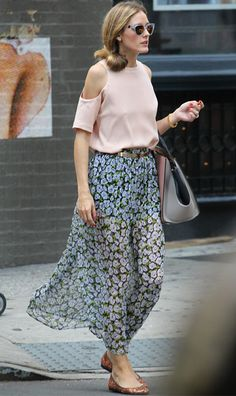 Olivia Palermo wears a flowy floral skirt with a pink cutout top, brown flats, a grey handbag, and sunglasses
