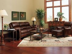 Brown leather sofa set for living room with dark hardwood floors