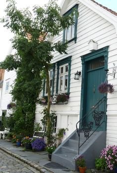 Door and cosiness in the old town of Stavanger in Norway, which has Europe's largest collection of wooden house - about 8.000. All possible styles - from empire to art nouveau and functionalism. That's what we call the timber city and here lives 30.000 people. - From THE ESSENCE OF THE GOOD LIFE™     http://www.pinterest.com/ConceptDesigner/   https://www.facebook.com/pages/The-Essence-of-the-Good-Life/367136923392157