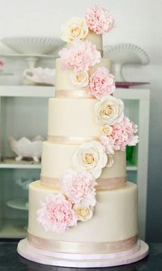 Stunning off white deep tiered cake with fresh blush and lemon flower embellishment.