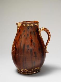 Pitcher  Date:1821 Geography:Probably made in Pennsylvania, United States; Probably made in New England, United States Culture:American Medium:Earthenware; Redware with slip decoration Dimensions:12 in. (30.5 cm) Classification:Ceramics Credit Line:Funds from various donors, 2008 Accession Number:2008.252 The elaborate slip decoration on this impressive presentation piece emulates the English tradition and relates to engraving found on silver and glass objects.