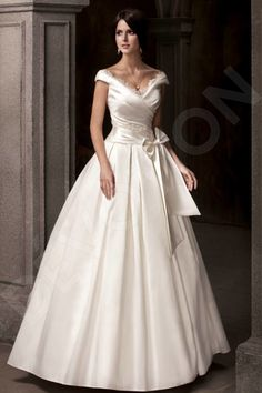 Stun everyone in this gracious and luxurious wedding gown.  The soft and simple cut of this satin and taffeta dress will make you beam with elegance, and the lace inserts on the neckline and bodice will accentuate the delicate curves of your neck and shoulders.  The bow around the waistline highlight the curve of your waist and provides the finest of finishing touches, making you a truly striking bride.  *The price doesn't include accessories.