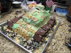 Military birthday with army tank. Rectangular cake, two layers then bread pan cake and cupcake on top, white chocolate covered pretzel for gun, sprayed green. Hershey's fun size chocolate and oreos for wheels and runners. Army men on cookie sheet around.