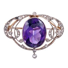 Classic Edwardian platinum over yellow gold housing a large oval faceted amethyst and decorated with 33 rose cut diamonds set in feminine open work. The piece is finished with a pin back and a bale. True antique jewel-toned finery.