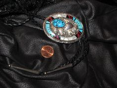 Incredible sterling silver, turquoise, coral, onyx and mother-of-pearl Navajo bolo tie. This piece measures 2 1/2 inches high by 1 3/4 inches wide.