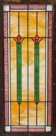 early 20th century antique american arts & crafts or craftsman style interior residential leaded art glass window possibly fabricated by the foster-munger co., chicago, il. the variegated slag glass window features a rectilinear grid comprised largely of caramel slag outlined with a textured white opalescent and pink border. the two matching centrally located abstract floral motifs contain long and narrow green stems with sectional orange-red flower motifs.
