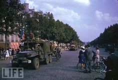 PARIS, FRANCE - AUGUST 26: American Army trucks (note cyclist hitching a ride) parading down the Champs Elysees the day after the liberation of Paris by Allied troops. (Photo by Frank Scherschel/Time & Life Pictures/Getty Images)