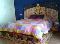 tête de lit palette de bois teinté, murs bleu marine, literie multicolore et sol en parquet massif