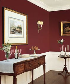 Handsome crown molding and wainscot pop against a deep coating of red in between the trim. @dunnedwards Deep Crimson (DEA152)