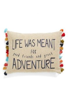 "Colorful tassels trim the sides of a decorative pillow with embroidery that reads, ""Life was meant for good friends and great adventure."""