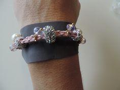 Bracciale in eco-pelle intrecciata di colore rosa e fettuccia grigia, con charm argento, pendenti con cristalli di colore lilla e perle di fiume. Chiusura dorata con moschettone.