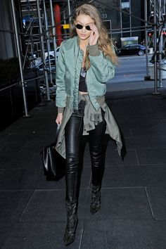 Gigi Hadid made her way around New York in a pair of black leather trousers and a green bomber jacket.